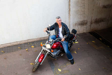 Horizontal color landscape from an elevated POV of a senior gray haired caucasian motor cycle rider on a red cruiser  Generic shot location in Bombay India  Model release available