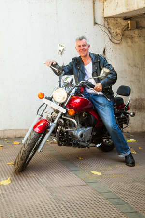 Vertcial take of a smilig senior caucasian male motorbike rider sat on a red cruiser wearing leather jacket in a relaxed pose  Generic shot location Bombay India Stock Photo