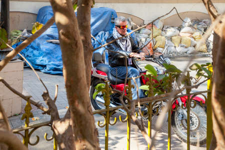 Horizontal color landscape capture of a senior caucasian male motorbike rider POV through trees and railings on a red cruiser wearing leather jacket in a relaxed pose   Generic shot location Bombay India with model release