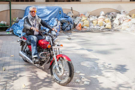 Horizontal color landscape capture of a senior caucasian male motorbike rider sidewalk POV on a red cruiser wearing leather jacket in a relaxed pose   Generic shot location Bombay India with model release