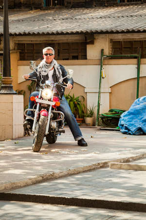 Color vertical portrait of a trendy fashion driven senior motor cyclist sat back on  a red cruiser smiling neautral espression in lether, denim, scarf and sunglasses  Generic shot location Bombay India with model release photo