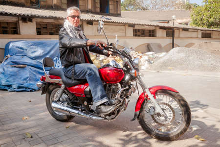 color horizontal landscape of a trendy fashion driven senior motor cyclist sat back on  a red cruiser smiling neautral espression in lether, denim, scarf and sunglasses  Generic shot location industrial backdrop Bombay India with model release photo