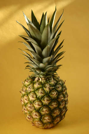 Pineapple and grapes on yellow background