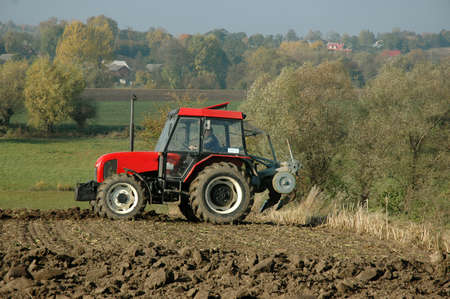 plough land: Tractor at work on a field. Stock Photo