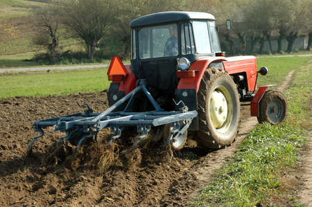 plough machine: Tractor at work on a field. Stock Photo