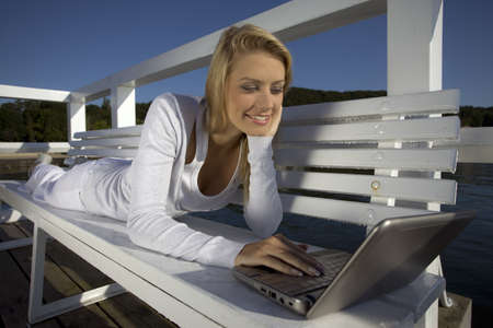 young woman with a laptop on the pier photo