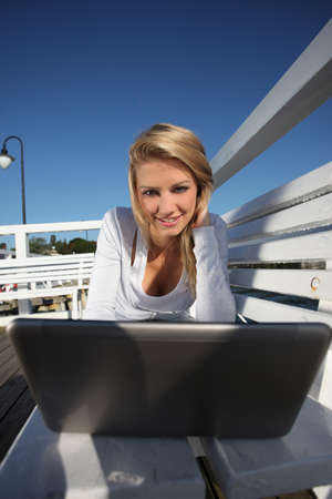 young woman with a laptop on the pier Stock Photo - 14938260