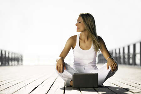 young woman with a laptop on the pier