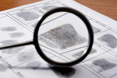 evidence bag: Magifying glass inspecting a fingerprint