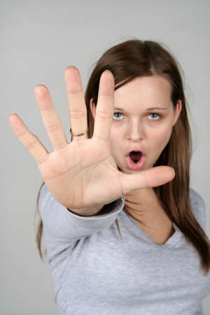 Young woman holding out her hand and screaming,  NO