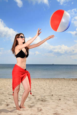 Girl playing beach volleyball by the sea.