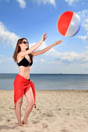 Lány játszik strandröplabda a tenger. Stock fotó