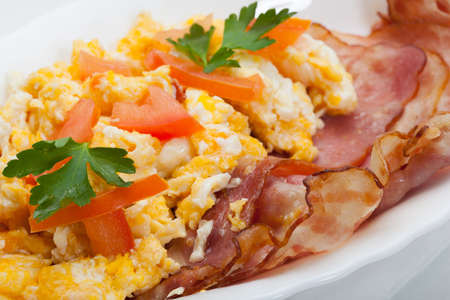 scrambled eggs with slices of bacon photo