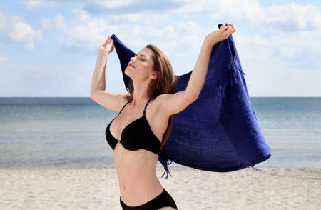 Young woman on the beach holding a scarf in her hands raised up