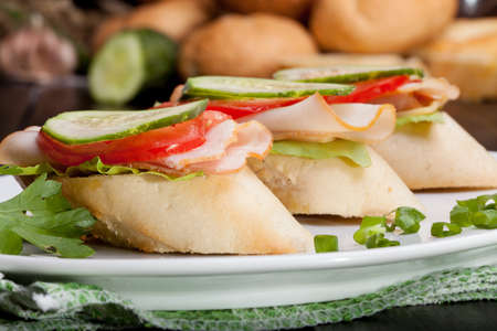 Three small sandwiches with ham and vegetables. photo