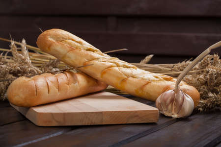 Baguettes lying on a wooden chopping board.