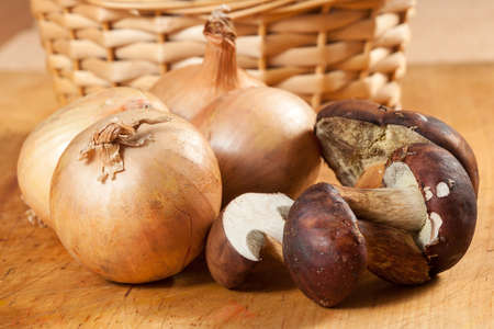 Onions and mushrooms on a wooden board
