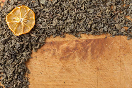 Dried leaves of green tea on a wooden board. Stock Photo