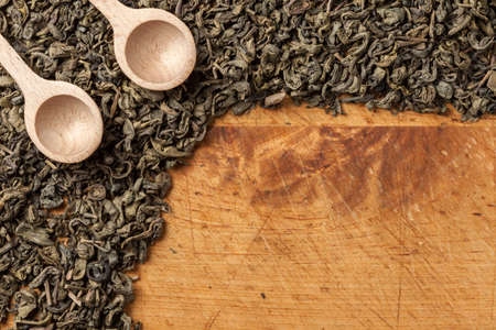 Spoon of dried green tea leaves on wooden background.