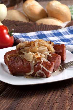 Fried sausage with onions on a plate. Stock Photo