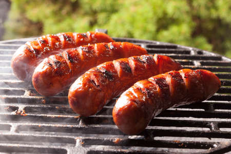 Grilling sausages on barbecue grill. Selective focus. Stockfoto