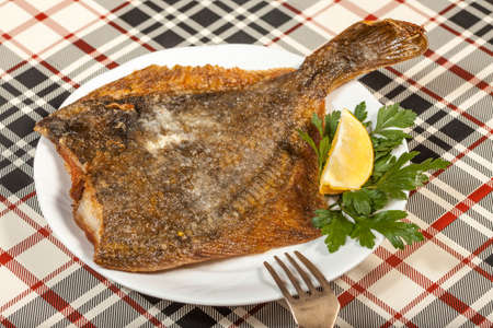 Fried flounder on a plate decorated with parsley and lemon. Selective focus. Standard-Bild