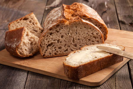 A slice of bread with butter on a chopping board. Stock Photo