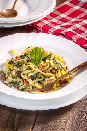 Spaghetti with spinach and bacon on a wooden table. Selective focus. photo