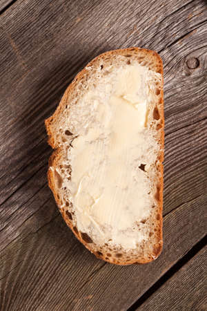 A slice of bread spread with butter. Stock Photo