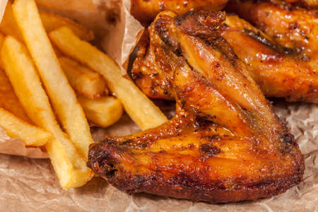 Roasted chicken wings and chips. Imagens