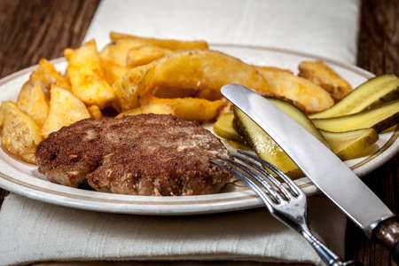 Fried chop, french fries and cucumber. Selective focus.