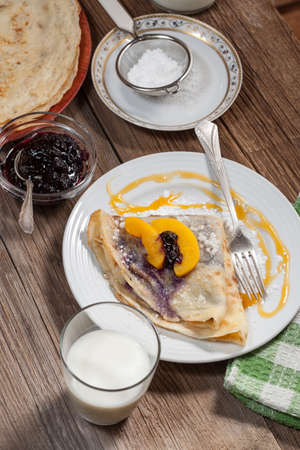 Pancakes with blackberry jam and cheese on a wooden background. Selective focus.