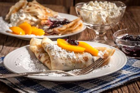 PANQUE: Panqueques con mermelada de mora y queso en un fondo de madera.