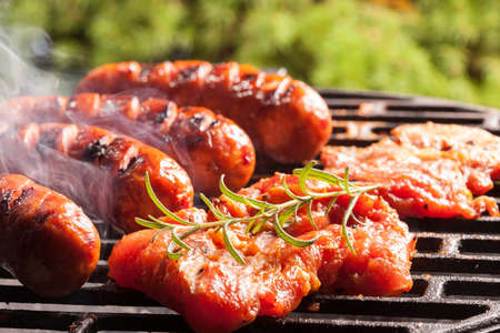 Grilling sausages on barbecue grill. Selective focus. Imagens