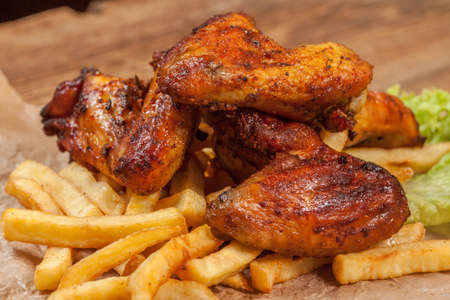 Roasted chicken wings and chips. Stock Photo