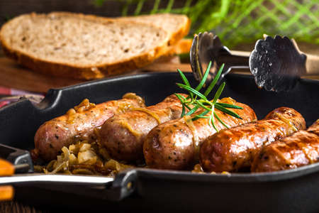 Fried sausages with onion in a pan.