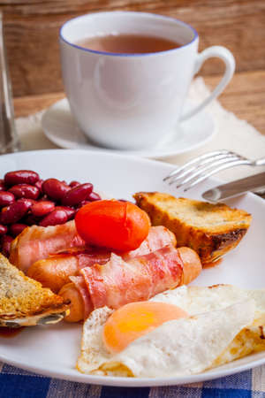 bacon baked beans: Full English breakfast with bacon, sausage, fried egg, baked beans and tea.