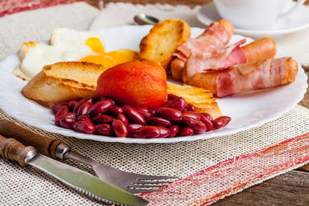 bacon baked beans: Full Angielski breakfast with fried egg bacon sausage baked beans and tea.