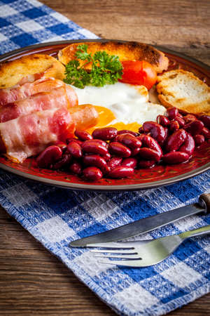 bacon baked beans: Full Angielski breakfast with bacon sausage fried egg and baked beans.