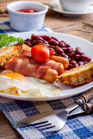 bacon baked beans: Full English breakfast with bacon, sausage, fried egg and baked beans.