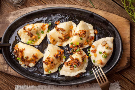 Dumplings with meat, onions and bacon on a cast iron skillet. Selective focus. Imagens - 44250365