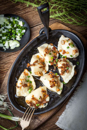 Dumplings with meat, onions and bacon on a cast iron skillet. Selective focus. Standard-Bild