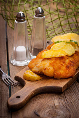 fish and chips: Fried fillet of cod with french fries on a wooden board. The selected focus point. Foto de archivo