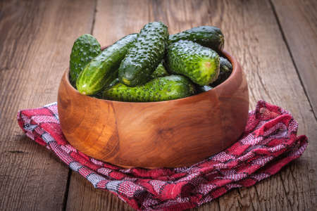 pickling: Fresh green pickling cucumbers in wooden bowl.