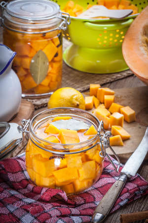 Pumpkin pickle in a glass container on a wooden table. Stock Photo