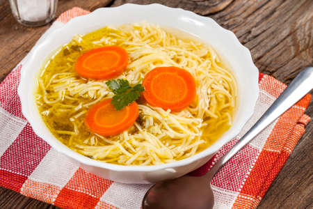 broth: Broth - chicken soup with noodles on a plate Stock Photo