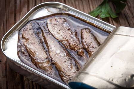sprats: Sprats in oil in a can on a wooden table.