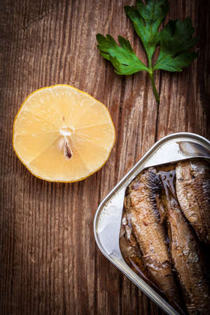 sardine can: Sprats in oil in a can on a wooden table.