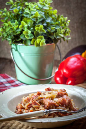 stewed: Stewed onions with sausage on a plate. Stock Photo