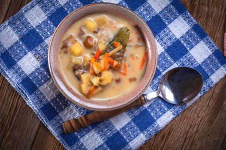 mushroom soup: Mushroom soup with vegetables on wooden table. Stock Photo